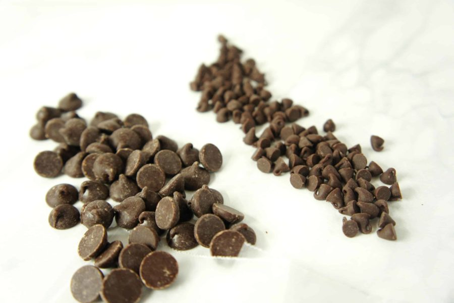A small pile of chocolate chips and a small pile of mini chocolate chips on a white table