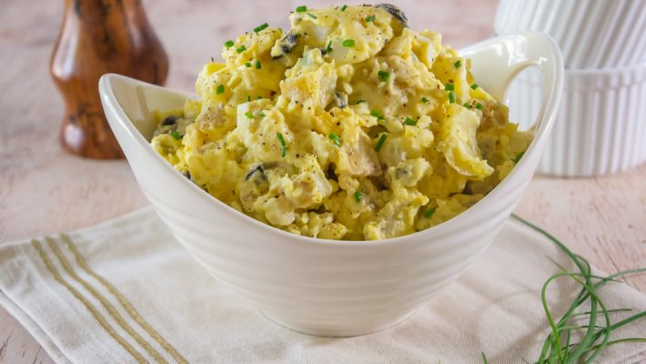 Potato salad with chives and black pepper on a napkin
