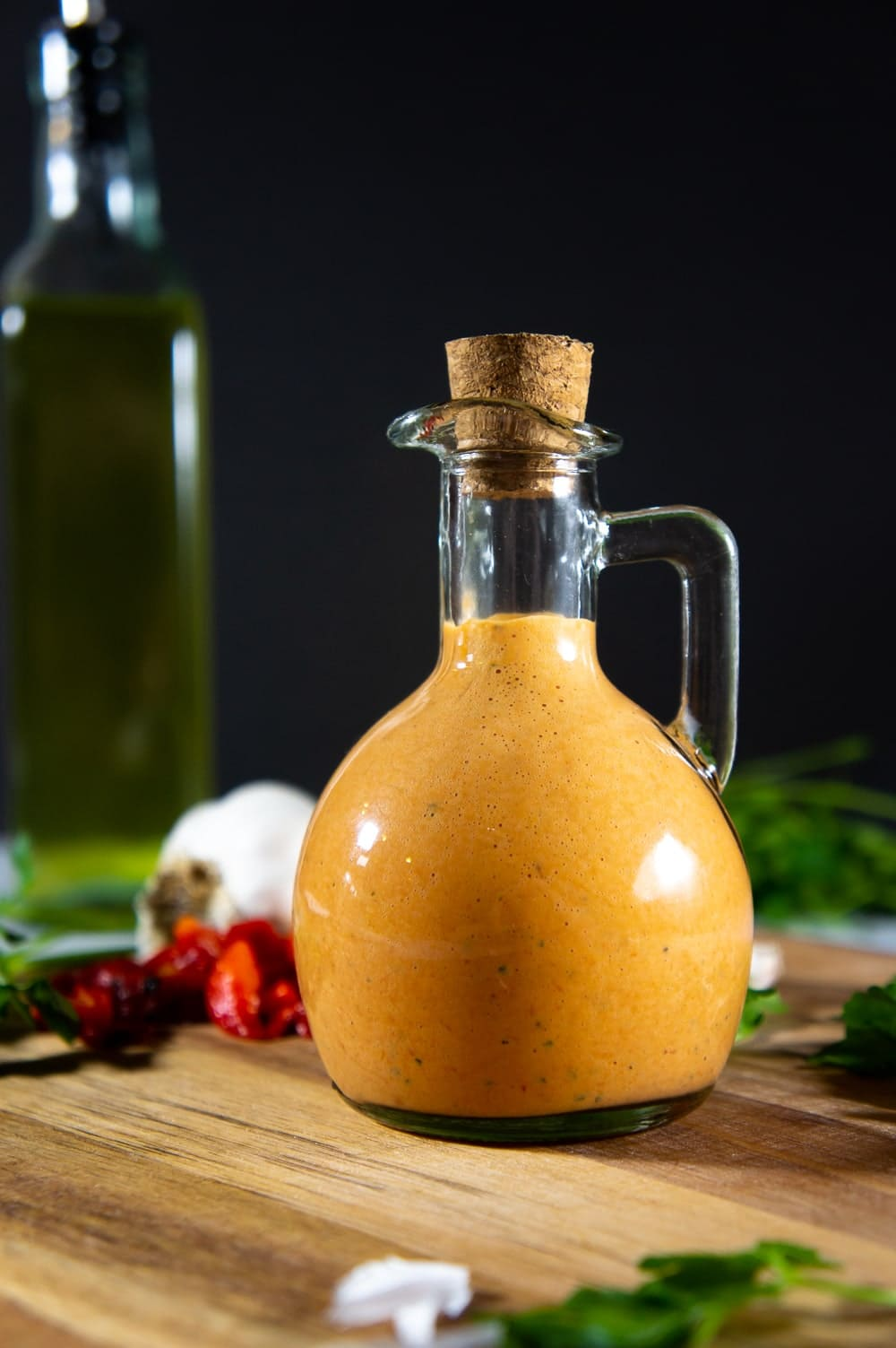 A jar of red pepper aioli on a wooden cutting board with parsley leaves