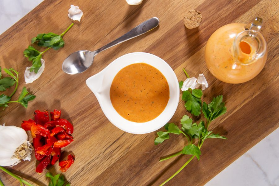 a bowl of red pepper aioli on a wooden cutting board