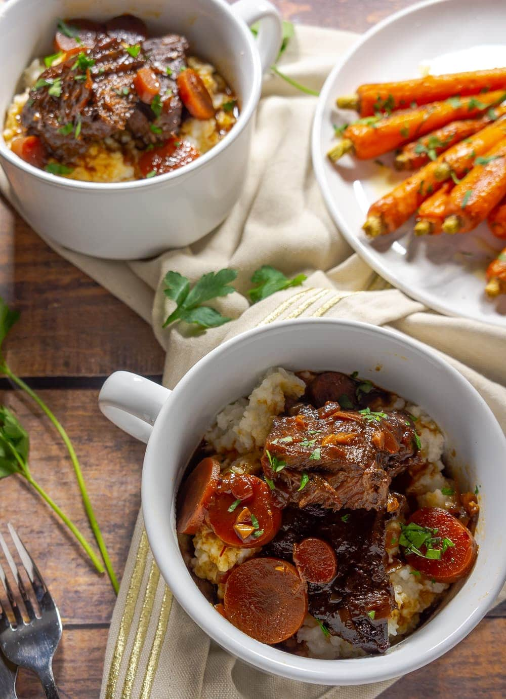 two white bowls of braised beef on a wooden table next to a plate of orange carrots