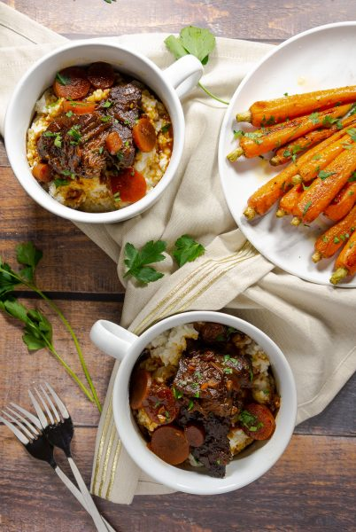 two bowls of braised short ribs and a plate of baby carrots