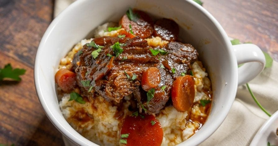 White bowl with braised beef over grits