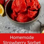 A bowl of strawberry sorbet surrounded by fresh strawberries and lemon wedges