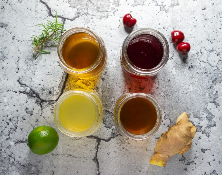 overhead of 4 jars of infused simple syrup