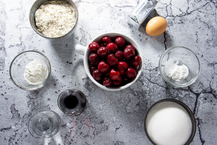 bowl of cherries, an egg, butter, flour, sugar, and red wine