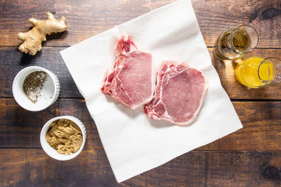raw pork chops beside orange juice, wine, salt, pepper, fresh ginger, and brown sugar
