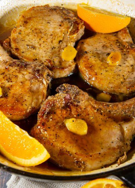 a pan of stove top pork chops in orange ginger sauce