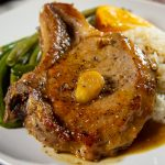 bone in pork chop on a white plate with green beans and white rice
