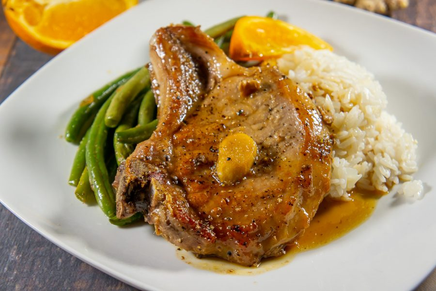 plate with bone in pork chops rice and green beans