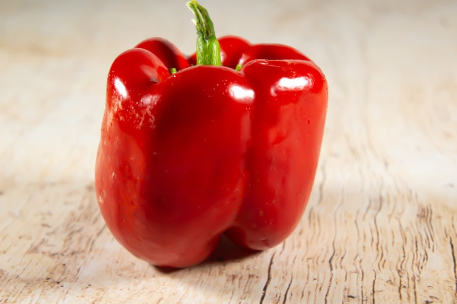 a red bell pepper on a wooden table