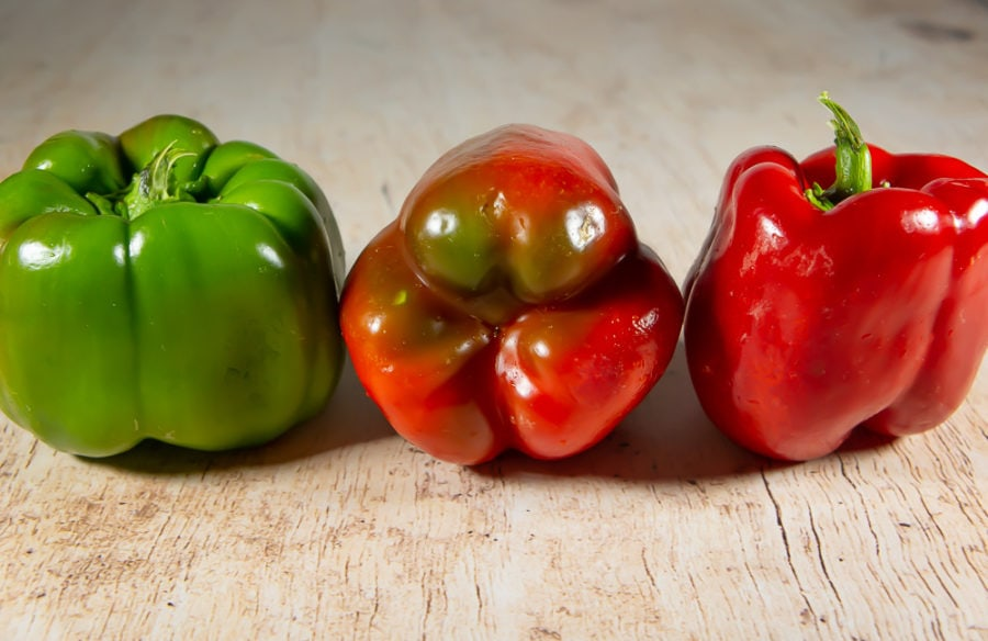 a green pepper, a green pepper turning red, and a red pepper on a table
