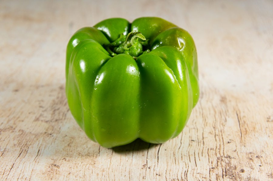 a green bell pepper on a wooden table
