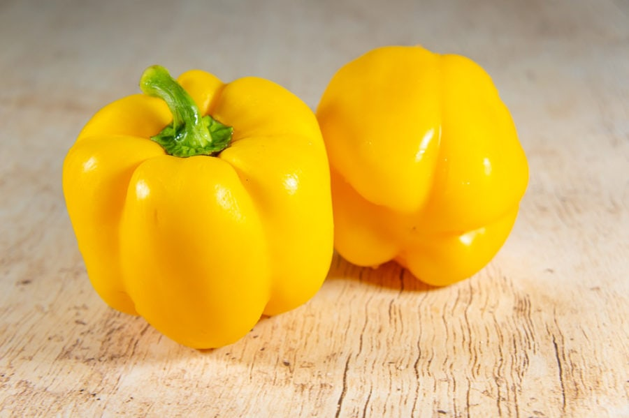 2 yellow bell peppers on a wooden table