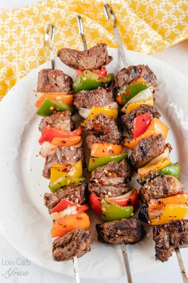 three skewers of beef and multicolored peppers