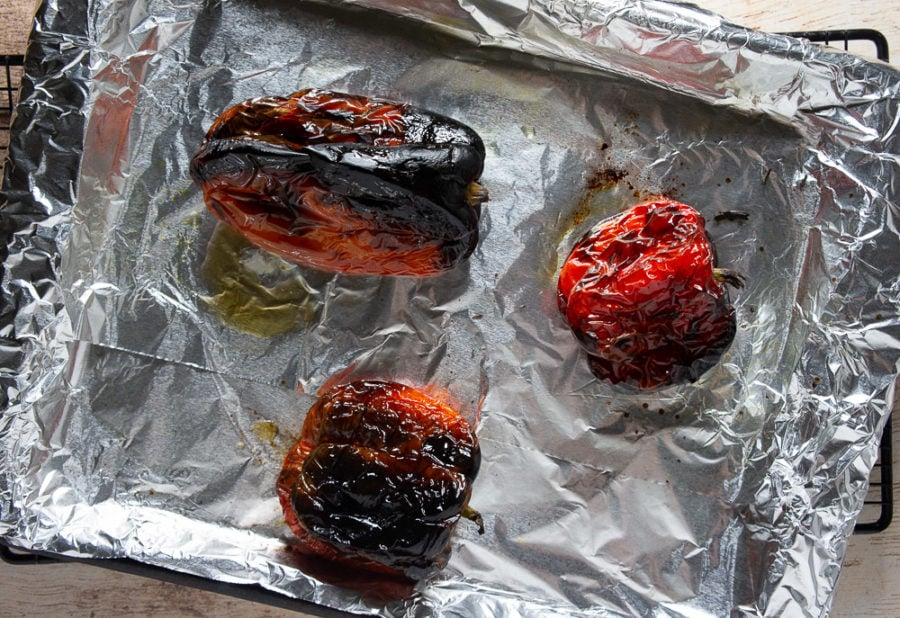 three roasted red peppers on a foil lined pan