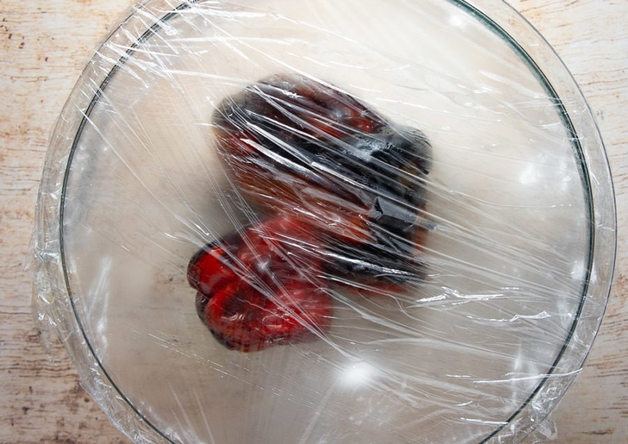 red peppers in a bowl covered by plastic wrap