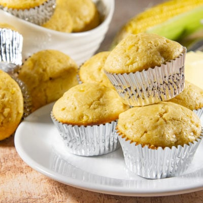 plate of cornbread muffins in front of a fresh corn on the cob and a bowl