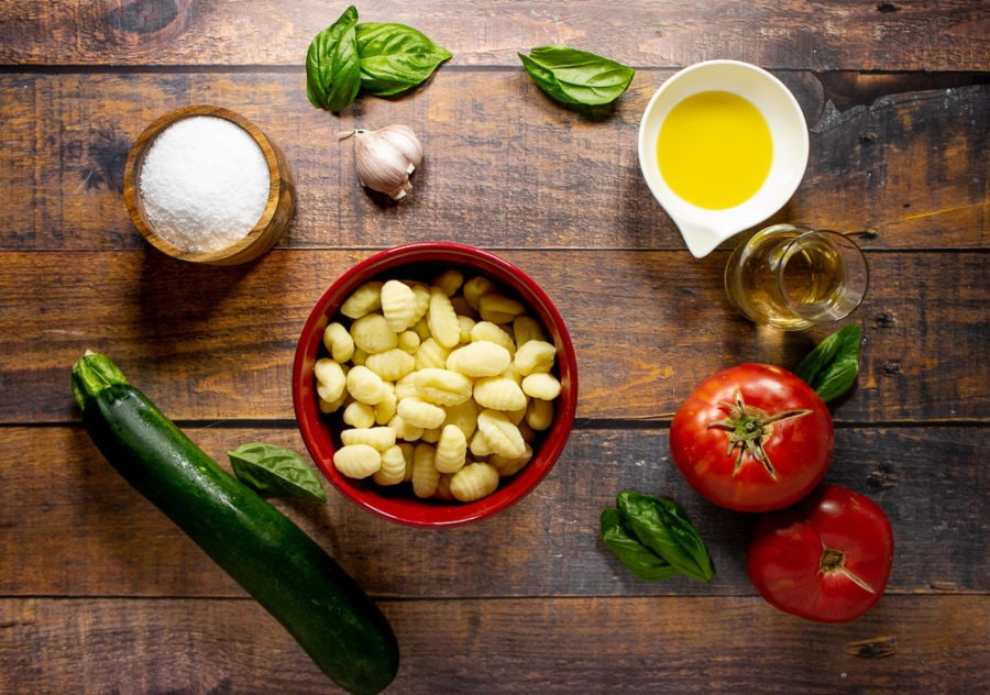 a bowl of uncooked gnocchi surrounded by basil, fresh tomatoes, zucchini, garlic, olive oil, white wine, and salt.
