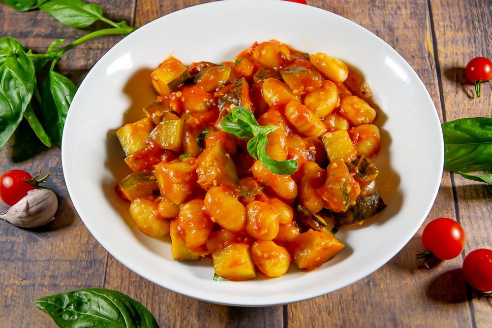 gnocchi in tomato sauce in a while bowl on a wooden table surrounded by basil and fresh tomatoes