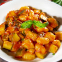 white bowl with gnocchi in tomato sauce and basil inside on a wooden table