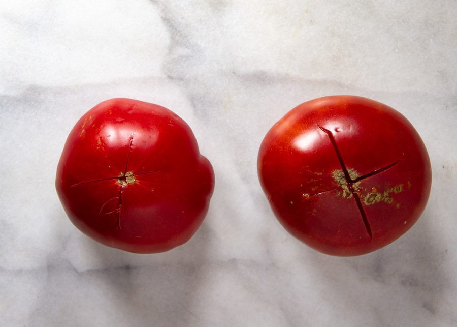 two tomatoes with shallow crosses cut in the bottom
