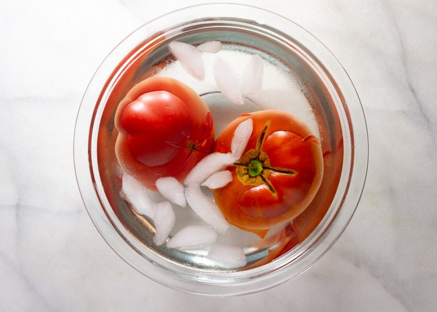 tomatoes submerged in a bowl of ice water