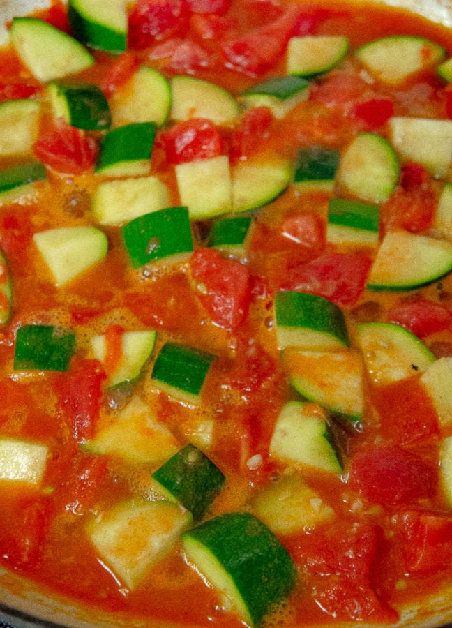 tomato and zucchini cooking in a large pan