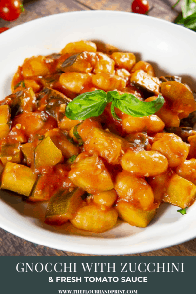 close up of a red sauce on gnocchi with zucchini and basil