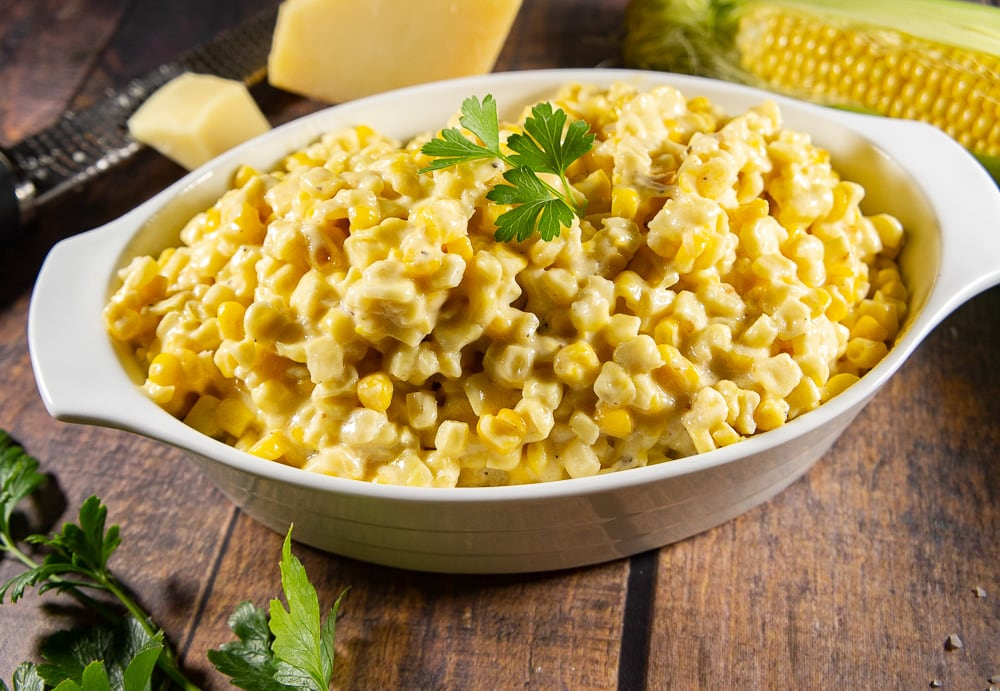 an oval bowl of creamy corn on a wooden table surrounded by parsley, parmesean cheese and a corn cob