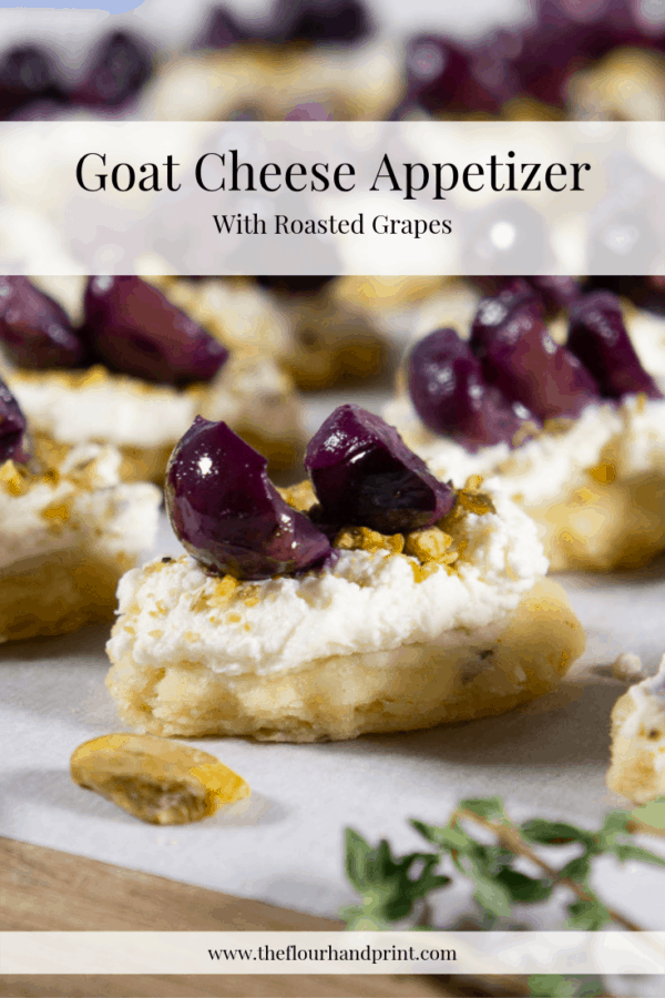 close up of a homemade cracker topped with goat cheese, pistachios, and roasted grapes