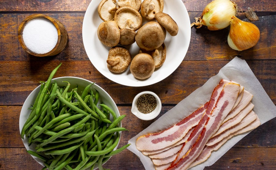a bowl of mushrooms, a bowl of green beans, and a plate of bacon next to onions, salt, and pepper on a wooden table