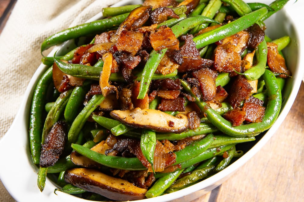 an oval bowl of green beans with mushrooms and onions
