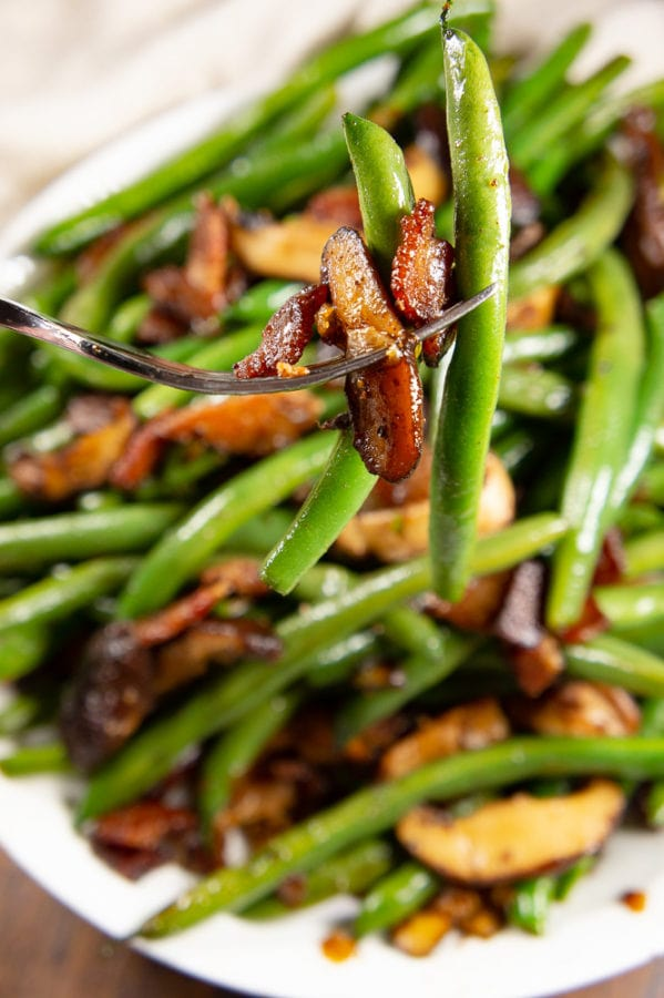a fork stabbing green beans and bacon