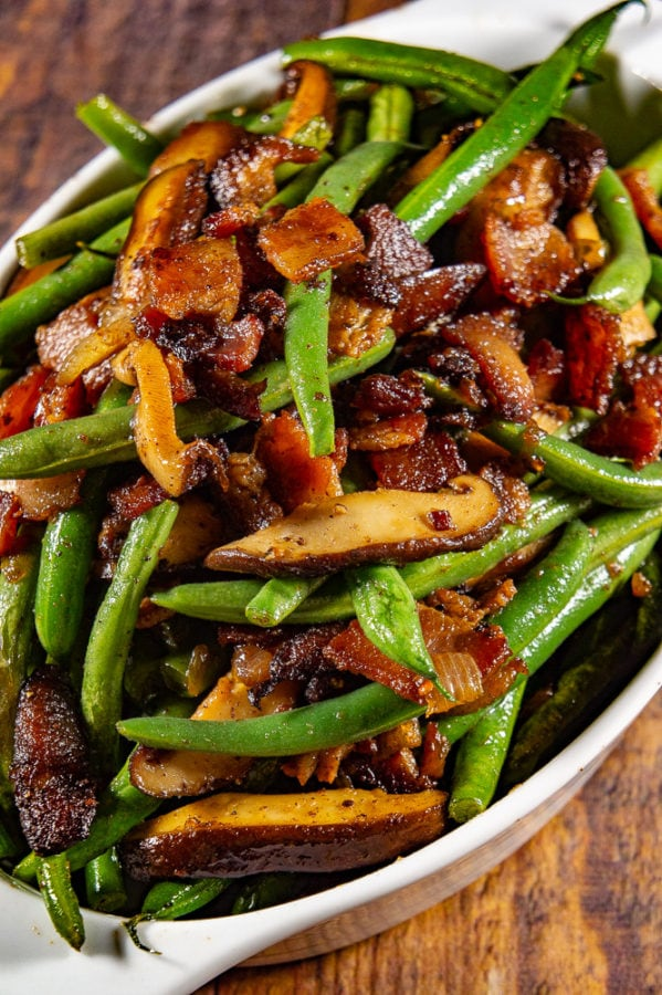 an oval white bowl of green beans with bacon, mushrooms, and onions on a wooden table