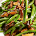 a forkful of green beans and bacon held above a platter of sauteed green beans