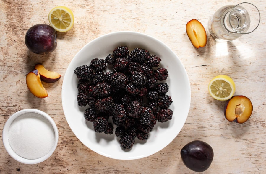 A white bowl of blackberries surrounded by sliced plums, lemon slices, a bowl of sugar and carafe of water