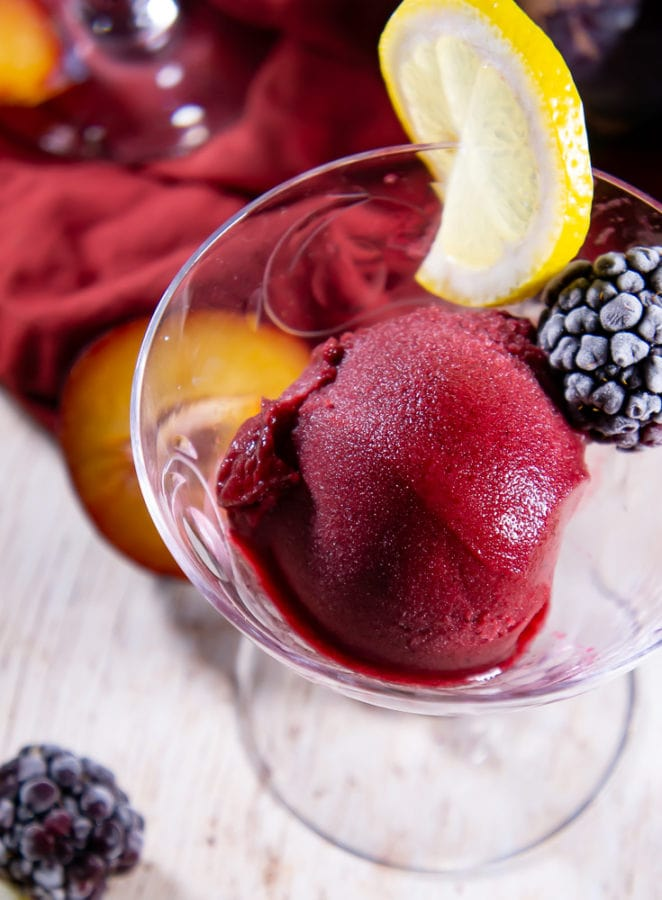 A dessert glass with a scoop of plum blackberry sorbet with a frozen berry and a lemon slice