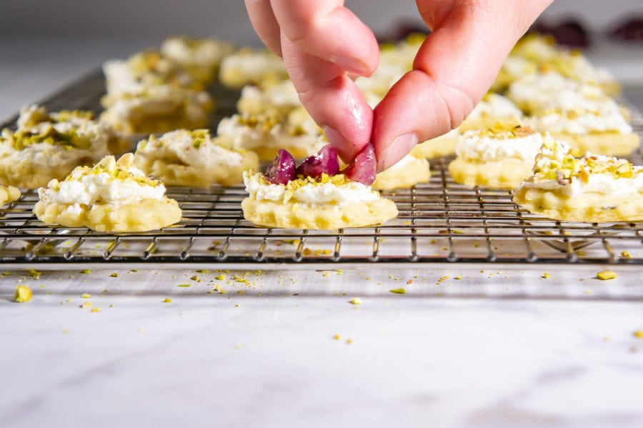 placing grapes on a goat cheese covered cracker