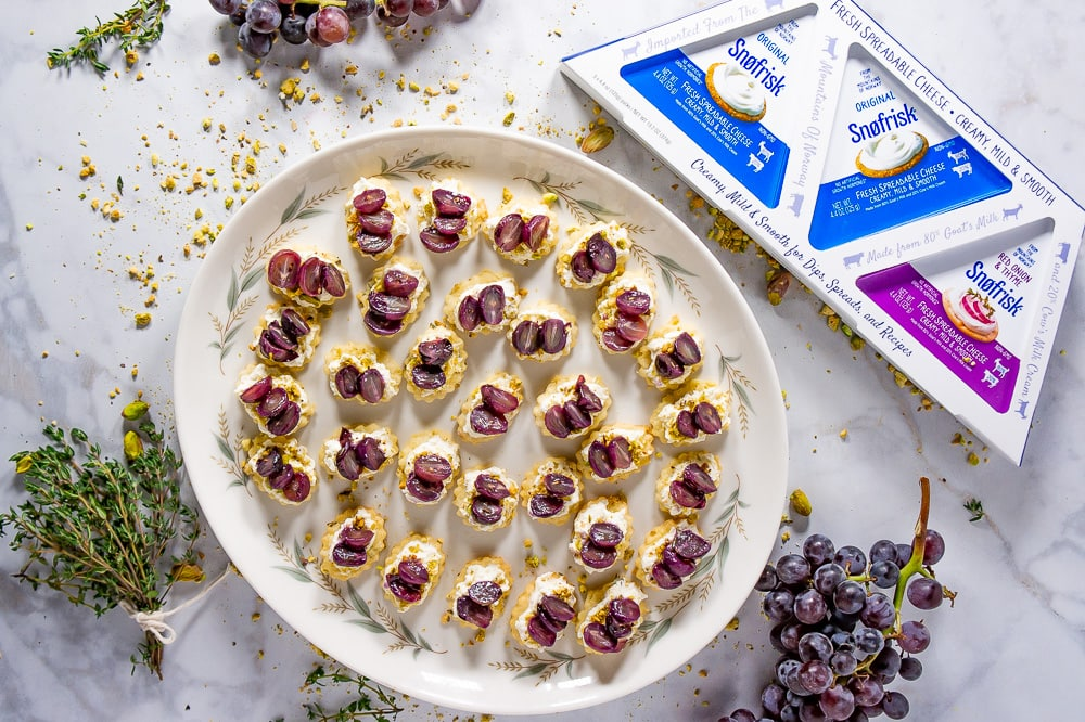 a platter of bite sized crackers topped with goat cheese, pistachios and grapes surrounded by thyme, grape clusters and goat cheese packaging