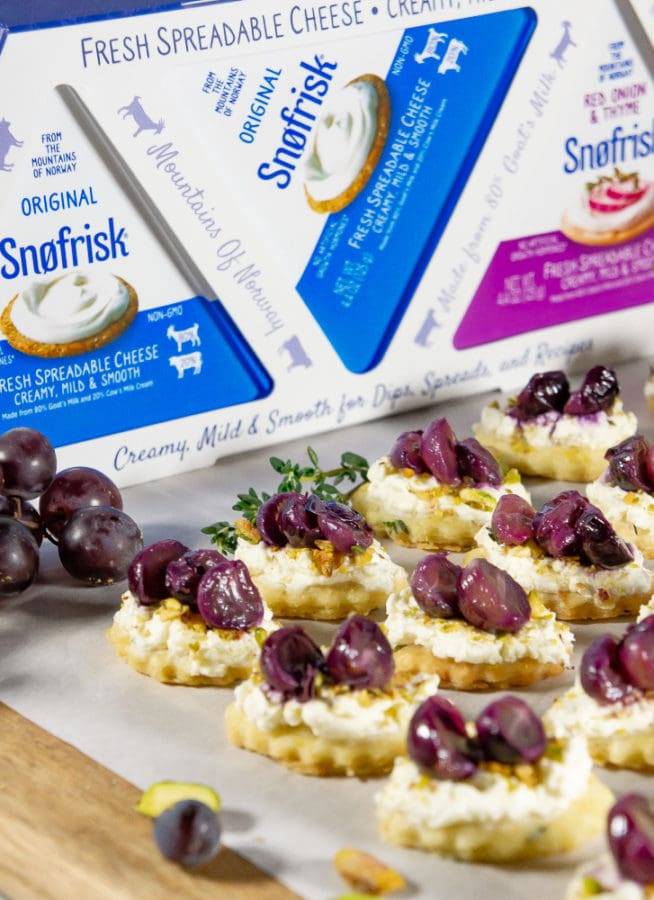 a serving board with goat cheese appetizers with roasted grapes in front of Snofrisk 3 pack