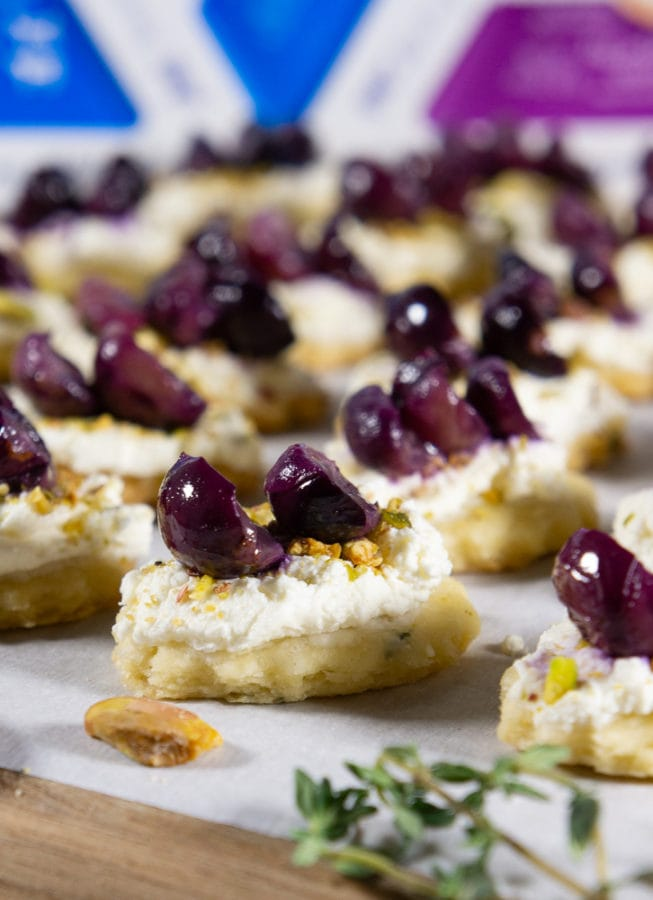 a close up of goat cheese appetizers with roasted grapes on top on a wooden board