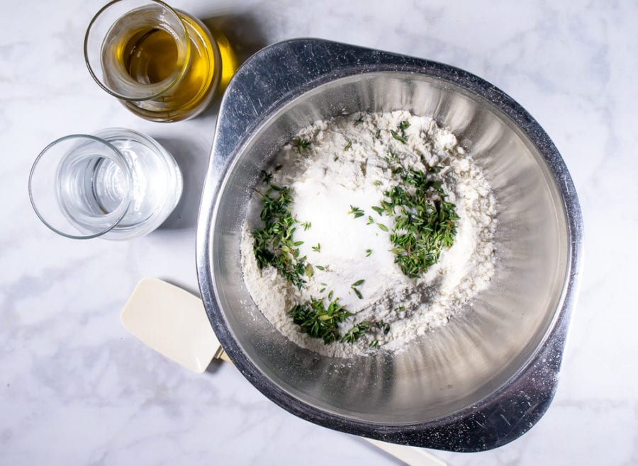 a metal bowl of flour, fresh thyme, sugar, and salt next to oil and water