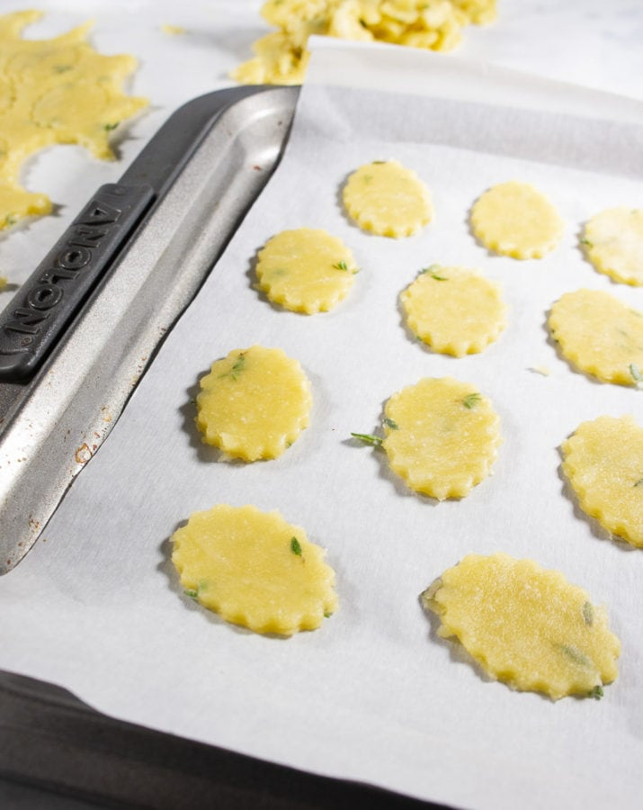 cracker dough rolled out and cut into ovals on a baking sheet with parchment paper