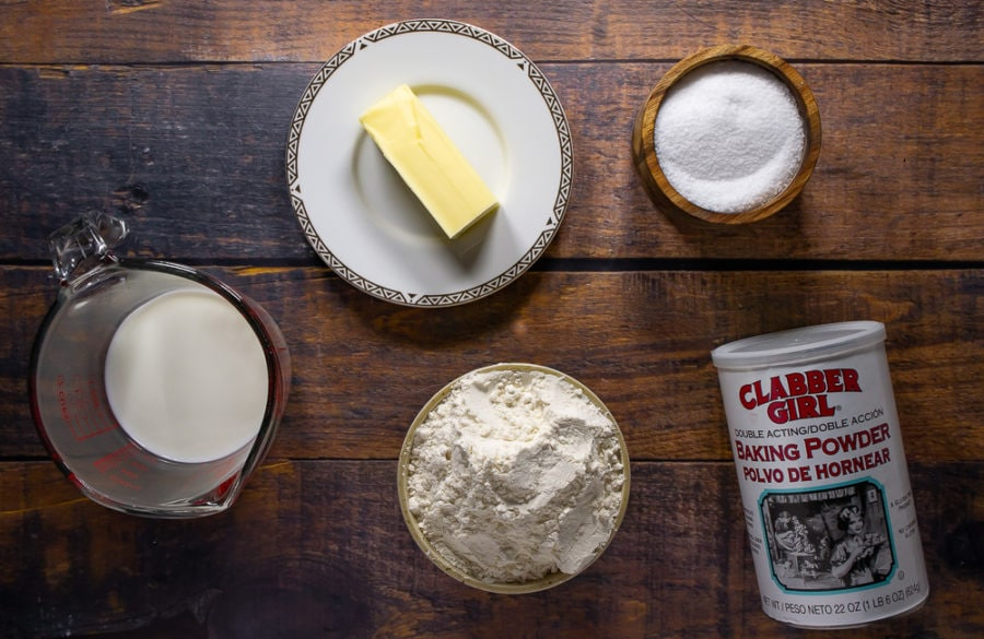 a bowl of flour, a stick of butter, a cup of milk, salt, and baking powder on a wooden table
