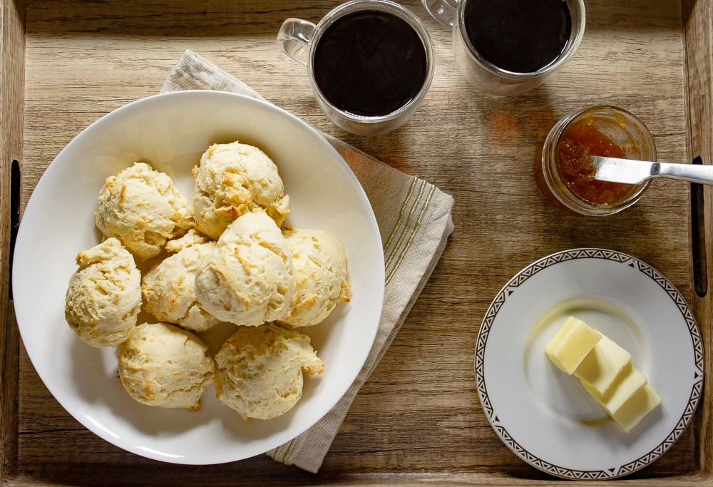a bowl of drop biscuits on a wooden serving tray with two cups of coffee, jam, and butter