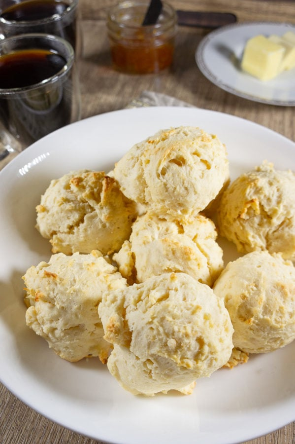a plate of biscuits on a tray with coffee, butter, and jam