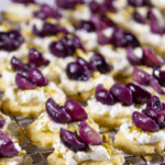 a metal cooling racking full of rows of crackers topped with goat cheese, pistachios, and roasted grapes