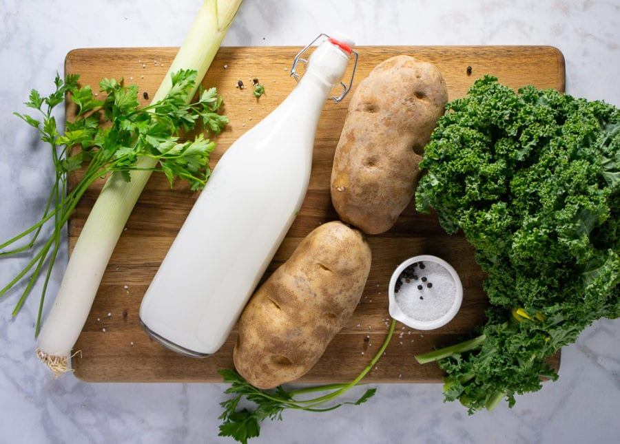 a wooden cutting board with a bunch of kale, two potatoes, a bottle of cream, a leek, and parsley