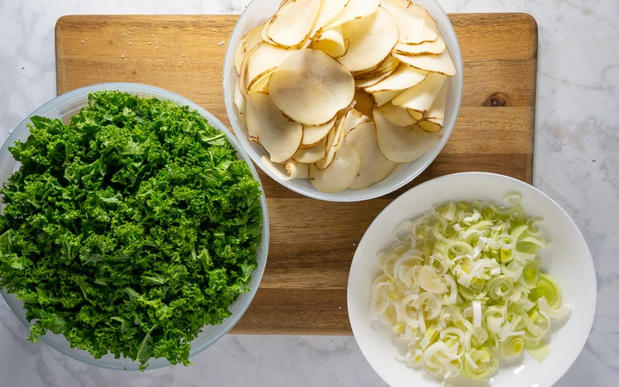 a bowl of kale, a bowl of thinly sliced potatoes, and a bowl of chopped leeks on top of a wooden cutting board on top of a white granite counter